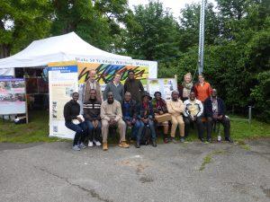 Vor dem Infostand versammelt die ganze Crew: 10 Gäste und die deutschen Begleiter der Gäste aus Mwanza. (Foto: Mwanza e.V.)